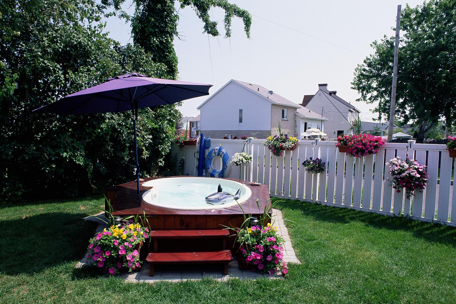 A hot tub in a back yard with umbrella and stairs