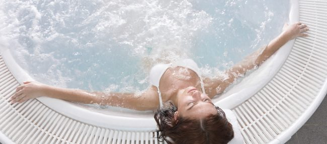 Young woman leaning back in hot tub with eyes closed