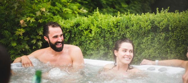 Smiling young couple enjoying their hot tub on a summer day