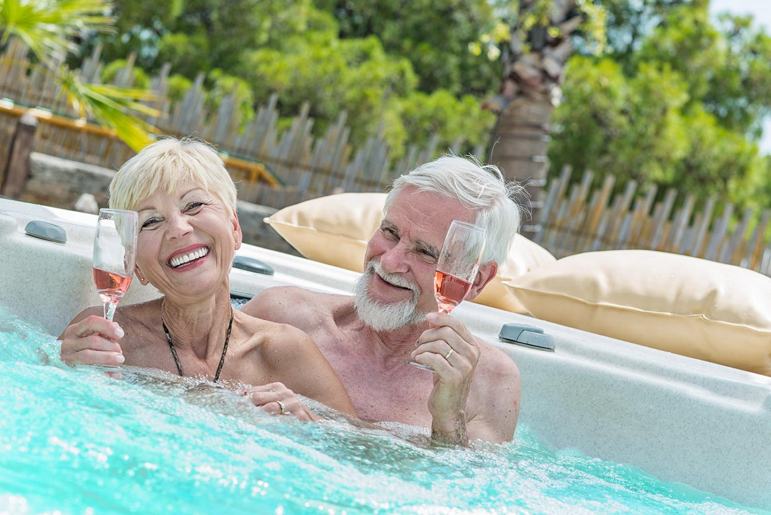 Senior couple drinking wine in hot tub