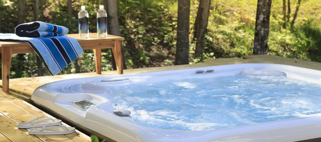 Hot tub on wooden deck with view of woods