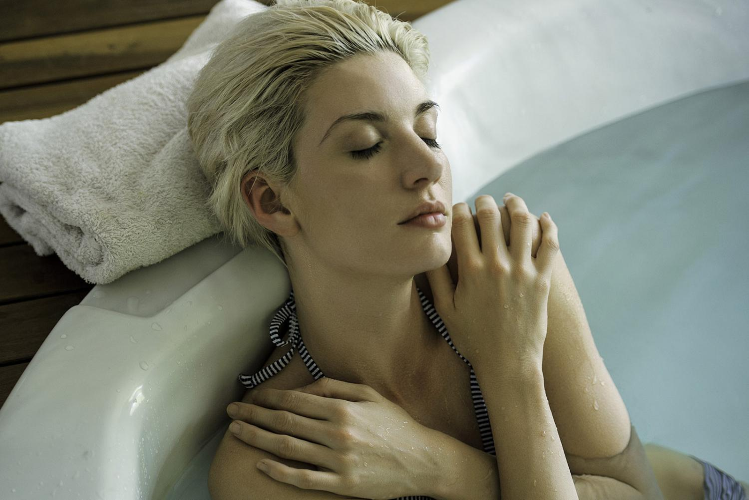 Woman with closed eyes relaxing in a hot tub