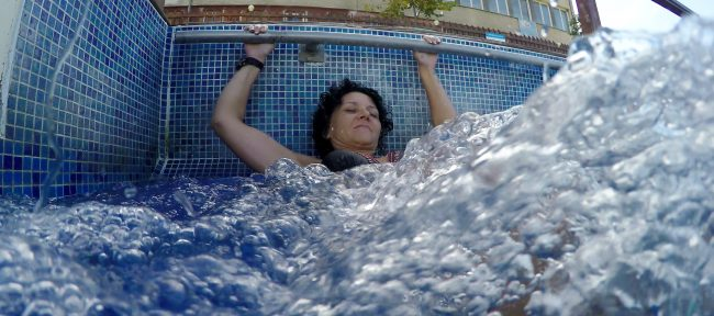 Woman doing scissor kicks in hot tub while holding on to the edge