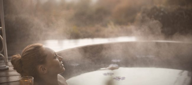 Woman relaxing in hot tub in autumn with steam rising off the surface of the water