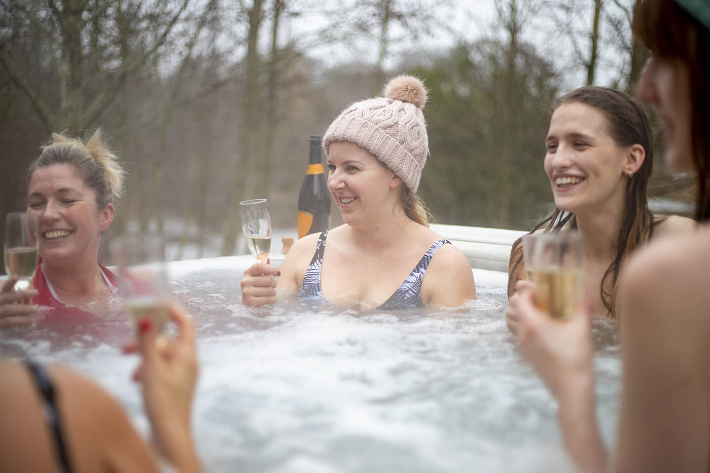 A group of female friends drink champagne in an outdoor hot tub surrounded by bare trees