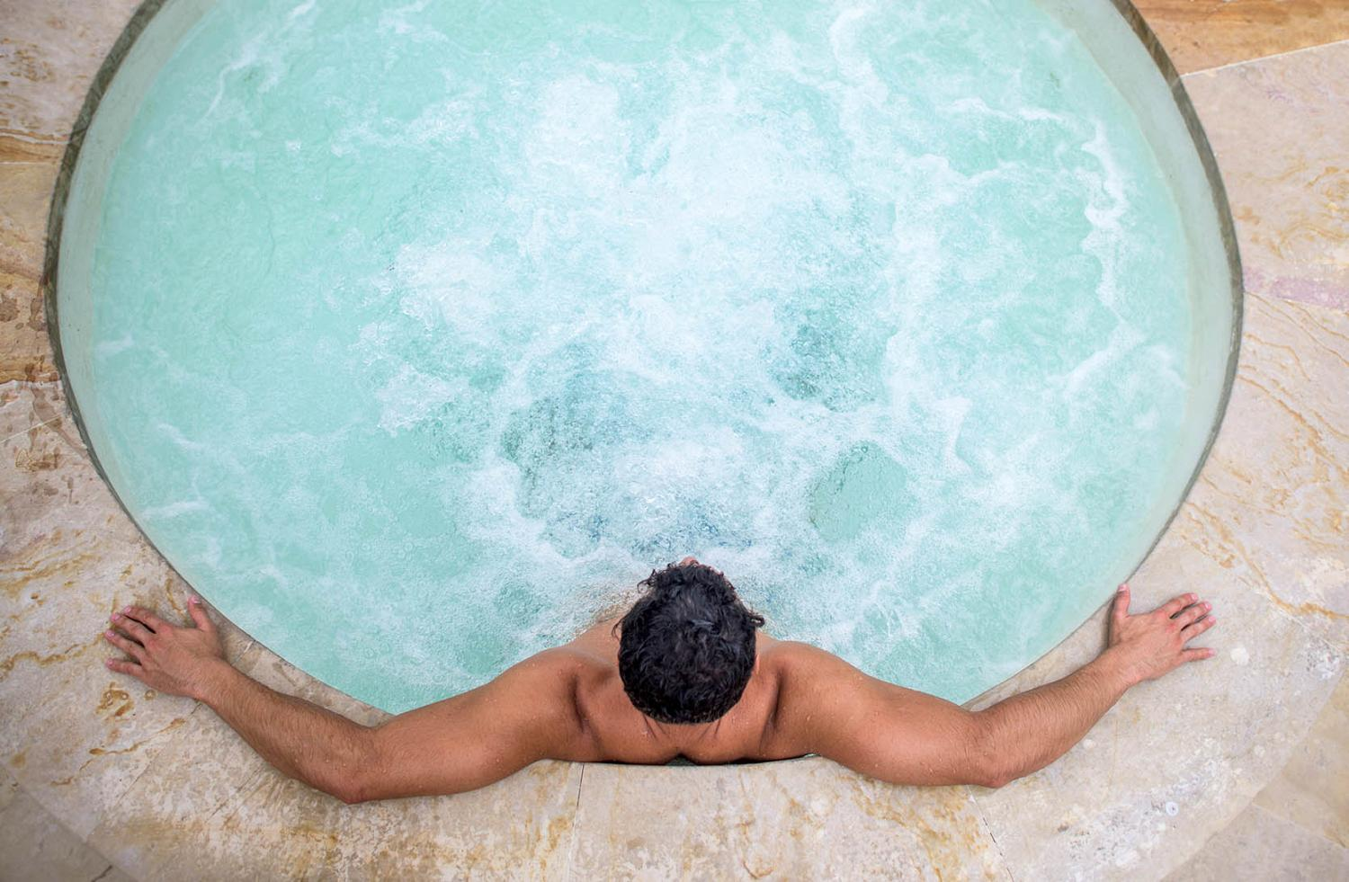 Man relaxing in a hot tub seen from above