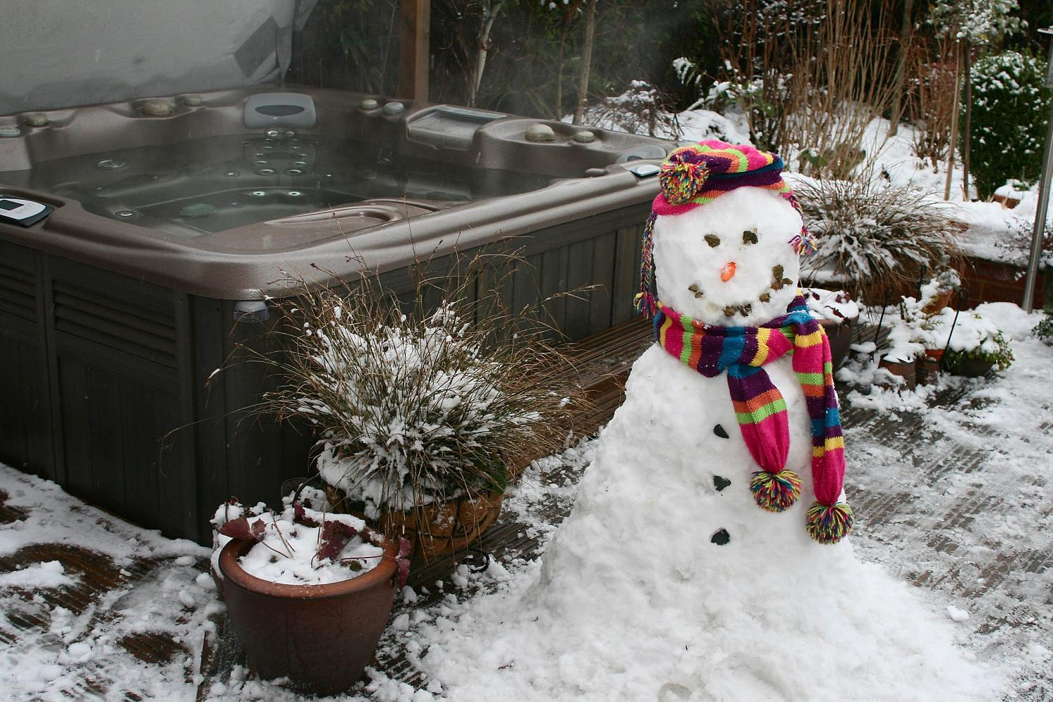 Hot tub spa outside with a snowman next to it