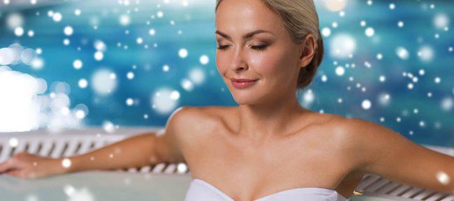 Beautiful woman wearing bikini sitting in hot tub with snow falling