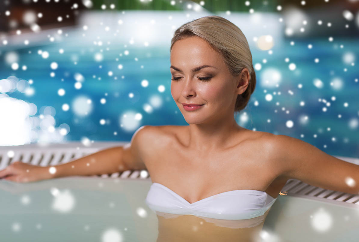 Beautiful woman wearing bikini sitting in hot tub with snow falling