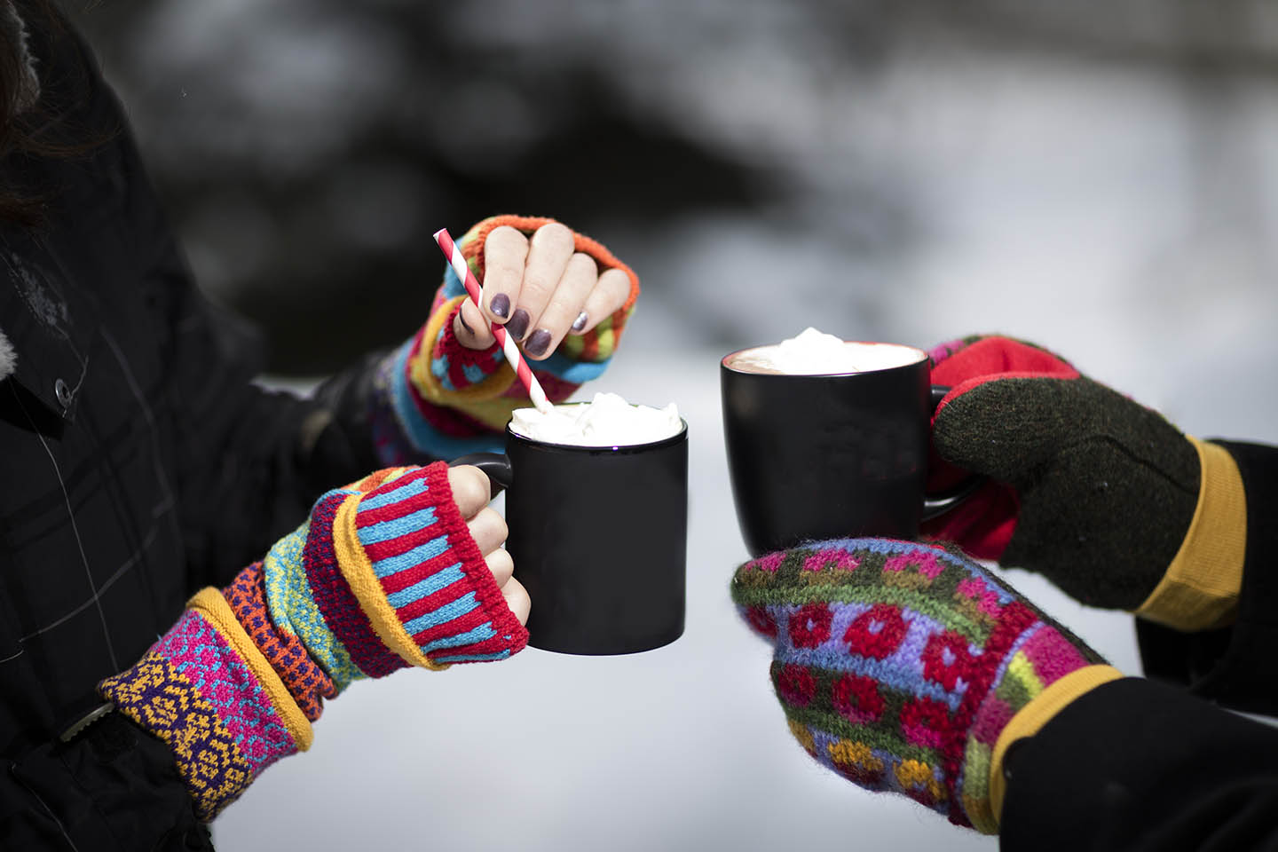 Two girls in fingerless gloves holding hot cocoa