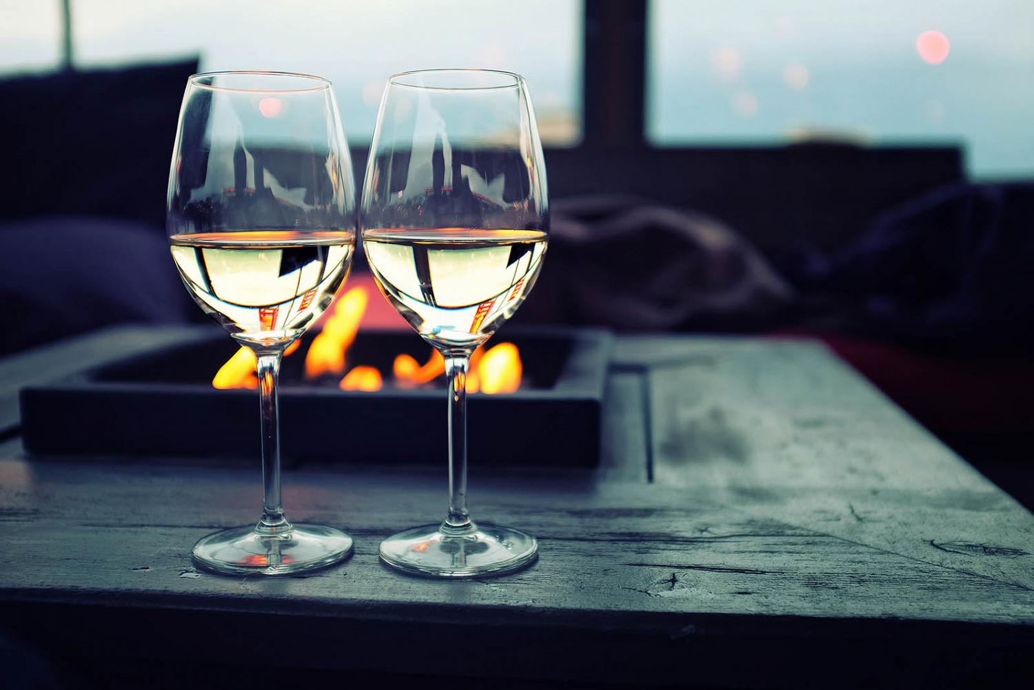 Two glasses of white wine near an outdoor fire