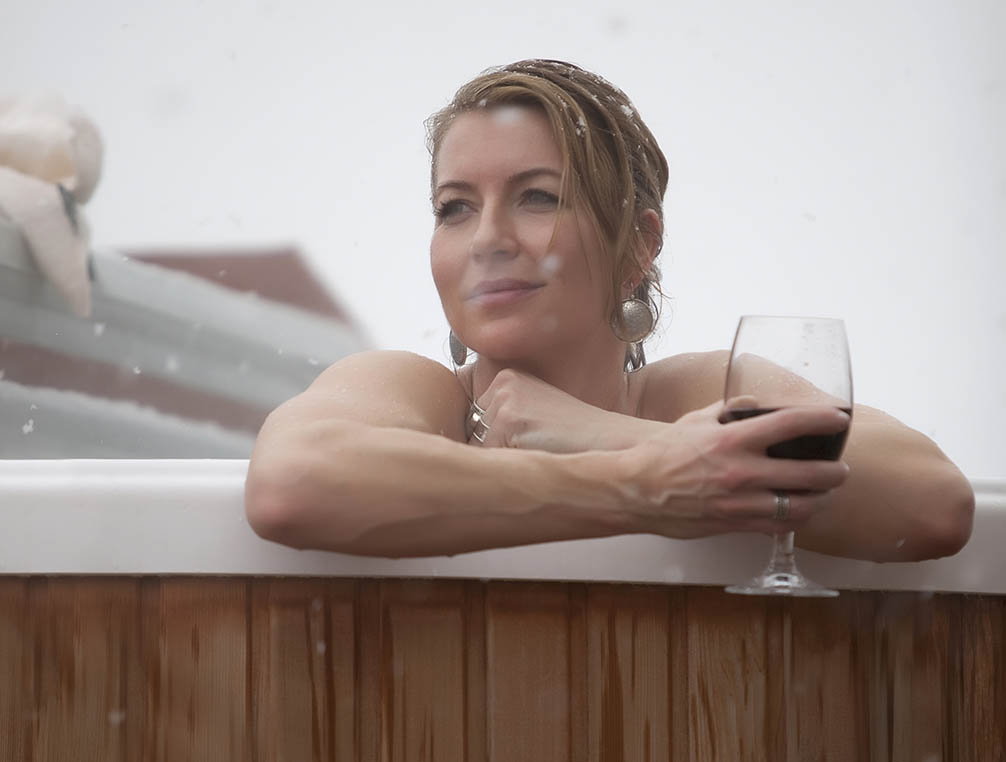 Woman in hot tub with glass of wine leaning against edge looking at snow
