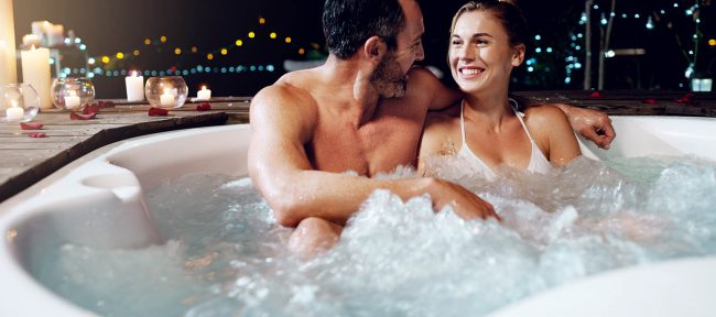 Smiling couple in hot tub with candles nearby
