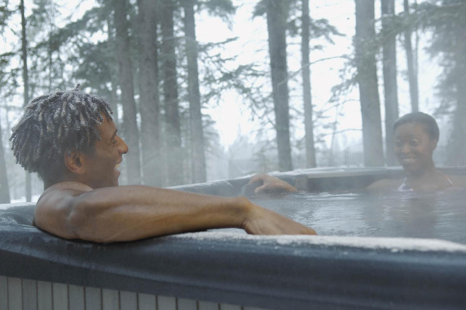 Smiling couple in outdoor hot tub in winter